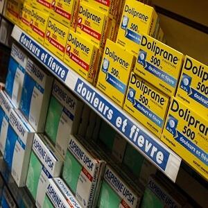 Boîtes de paracétamol (Doliprane), et d'aspirine (Aspirine UPSA et Efferalgan), exposées sur un rayon dans une pharmacie.